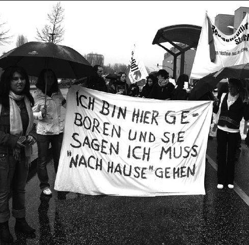 Frauen mit einem Transparent mit der Aufschrift: Ich bin hier geboren und sie sagen ich muss »nach Hause« gehen